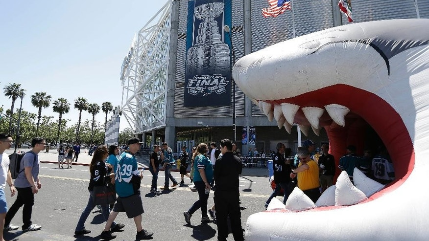 Fans walk outside of SAP Center at San Jose before Game 6 of the NHL hockey Stanley Cup Final series between the San Jose Sharks and the Pittsburgh Penguins in San Jose, Calif., Sunday, June 12, 2016. (AP Photo/Eric Risberg)