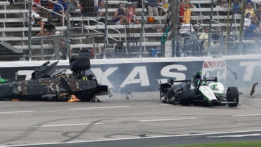 Josef Newgarden's car, left. slides down the track after being involved in a wreck with Conor Daly during an IndyCar auto race at Texas Motor Speedway, Sunday, June 12, 2016, in Fort Worth, Texas. (AP Photo/Tim Sharp)