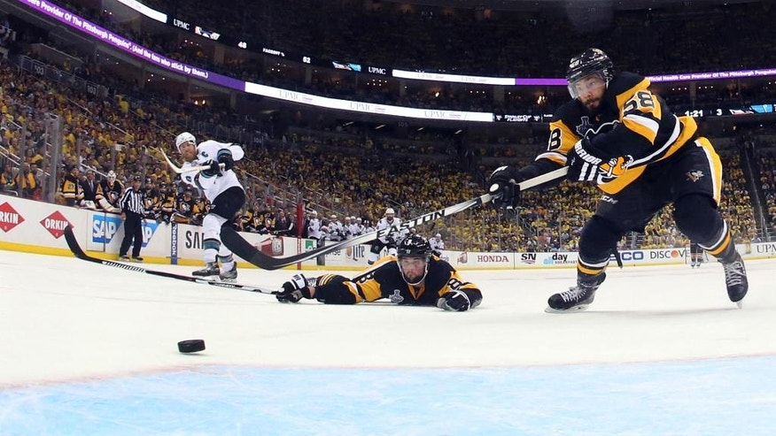 San Jose Sharks' Joe Pavelski (8) scores an empty-net goal past Pittsburgh Penguins' Brian Dumoulin (8) and Kris Letang (58) during the third period in Game 5 of the NHL hockey Stanley Cup Finals on Thursday, June 9, 2016, in Pittsburgh. The Sharks won 4-2. (Bruce Bennett/Pool Photo via AP)