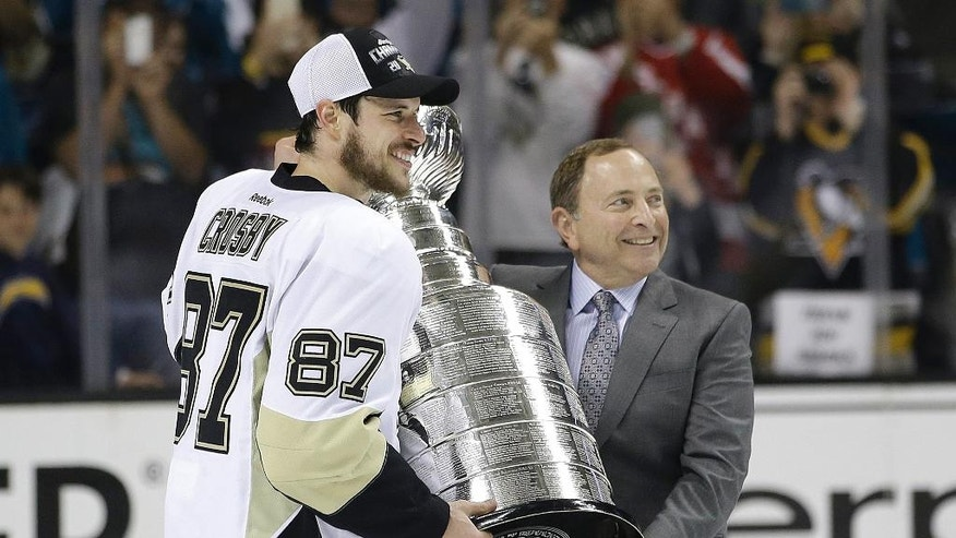 Pittsburgh Penguins center Sidney Crosby (87) is presented the Stanley Cup by commissioner Gary Bettman after Game 6 of the NHL hockey Stanley Cup Finals between the San Jose Sharks and the Penguins in San Jose, Calif., Sunday, June 12, 2016. The Penguins won 3-1 to win the series 4-2. (AP Photo/Marcio Jose Sanchez)