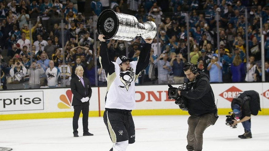 Pittsburgh Penguins center Sidney Crosby celebrates with the Stanley Cup after Game 6 of the NHL hockey Stanley Cup Finals against the San Jose Sharks in San Jose, Calif., Sunday, June 12, 2016. The Penguins won 3-1 to win the series 4-2. (AP Photo/Marcio Jose Sanchez)