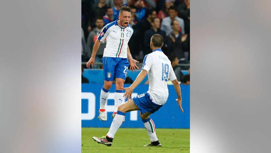 Italy's Emanuele Giaccherini, left, celebrates with teammate Leonardo Bonucci after scoring his side's first goal during the Euro 2016 Group E soccer match between Belgium and Italy at the Grand Stade in Decines-Charpieu, near Lyon, France, Monday, June 13, 2016. (AP Photo/Antonio Calanni)