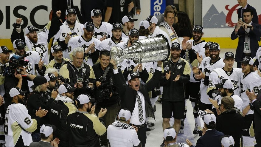 Pittsburgh Penguins head coach Mike Sullivan raises the Stanley Cup after Game 6 of the NHL hockey Stanley Cup Finals against the San Jose Sharks Sunday, June 12, 2016, in San Jose, Calif. The Pittsburgh Penguins won 3-1 to win the series 4-2. (AP Photo/Eric Risberg)