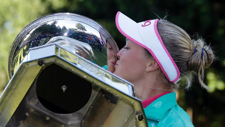 After being prompted by organizers, Brooke Henderson, of Canada, plants a kiss on the championship trophy after winning the Women's PGA Championship golf tournament at Sahalee Country Club on Sunday, June 12, 2016, in Sammamish, Wash. (AP Photo/Elaine Thompson)