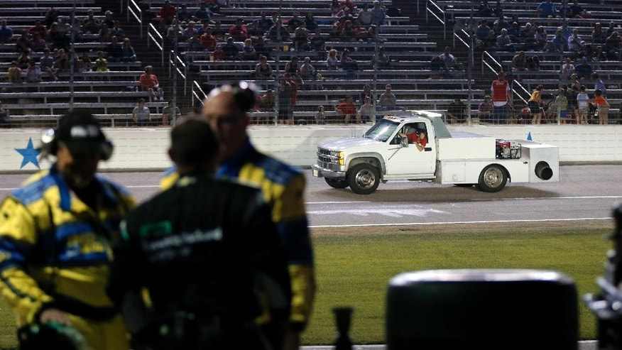 Race officials and a crew team member talk along pit road as a track employee drives a dryer slowly down the front stretch attempting to dry the track before an IndyCar auto race at Texas Motor Speedway, Saturday, June 11, 2016, in Fort Worth, Texas. (AP Photo/Tony Gutierrez)