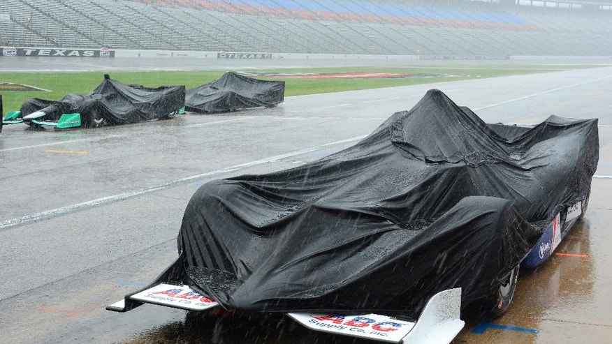 Race cars are covered by tarps during a thunderstorm which stopped an IndyCar auto race at Texas Motor Speedway, Sunday, June 12, 2016, in Fort Worth, Texas. (AP Photo/Larry Papke)
