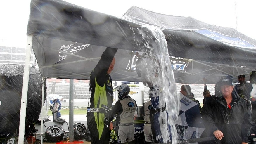 Crew members for Charlie Kimball drain the water from the roof of their canopy during a thunderstorm which stopped an IndyCar auto race at Texas Motor Speedway, Sunday, June 12, 2016, in Fort Worth, Texas. (AP Photo/Tim Sharp)