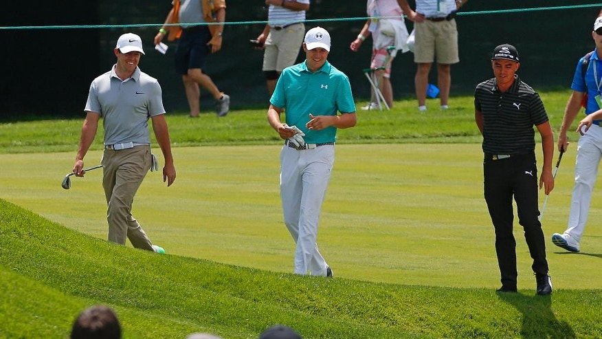 Defending U.S. Open Champion Jordan Spieth, center, walks up the 17th fairway with Rory McIlroy, left, of Northern Ireland, and Rickie Fowler during a practice round for the 2016 US Open golf championship at Oakmont Country Club in Oakmont, Pa., Monday, June 13, 2016. (AP Photo/Gene J. Puskar)