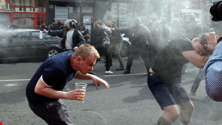 June 15, 2016: English fans run after getting sprayed with pepper spray by French police during scuffles in downtown Lille, northern France.