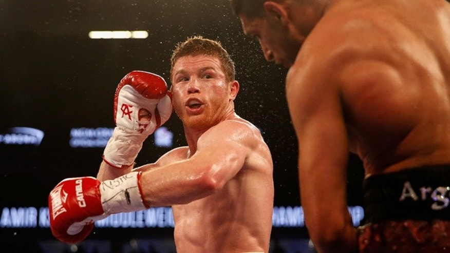 LAS VEGAS, NEVADA - MAY 07:  Canelo Alvarez (L) throws a left at Amir Khan during the WBC middleweight title fight at T-Mobile Arena on May 7, 2016 in Las Vegas, Nevada.  (Photo by Christian Petersen/Getty Images)