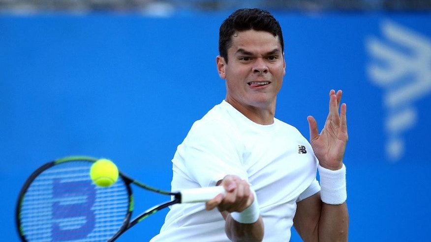 Canada's Milos Raonic returns the ball to Australia's Nick Kyrgios on day two of the Queen's grass-court tennis tournament in London, Tuesday June 14, 2016. (Steve Paston/PA via AP) UNITED KINGDOM OUT