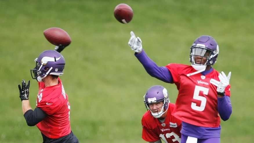 CORRECTS YEAR -Minnesota Vikings quarterbacks Teddy Bridgewater, right, and Taylor Heinicke throw during the NFL football team's minicamp Wednesday, June 15, 2016, in Eden Prairie, Minn. Watching, bottom center, is quarterback Shaun Hill. (AP Photo/Jim Mone)