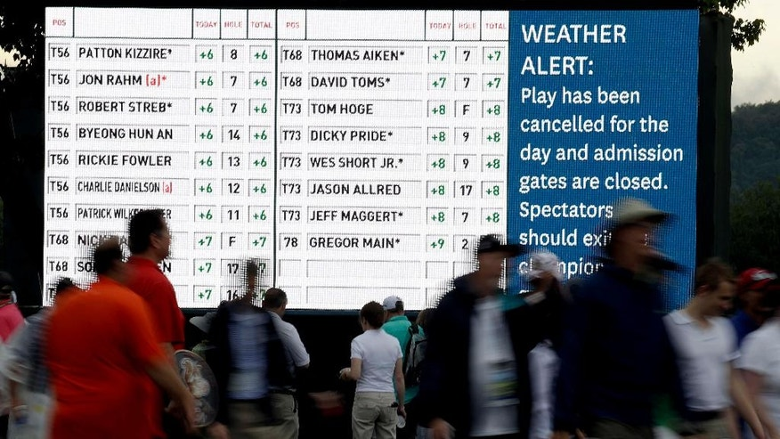 Fans leave the course during a rain delay in the first round of the U.S. Open golf championship at Oakmont Country Club on Thursday, June 16, 2016, in Oakmont, Pa. (AP Photo/Charlie Riedel)
