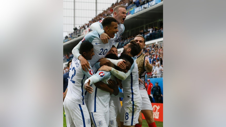England's Daniel Sturridge, center, is mobbed by his teammates after scoring his side's second goal during the Euro 2016 Group B soccer match between England and Wales at the Bollaert stadium in Lens, France, Thursday, June 16, 2016. Surrounding him are Wayne Rooney, top, Dele Alli (20), Marcus Rashford, bottom left, and Adam Lallana (8). (AP Photo/Kirsty Wigglesworth)