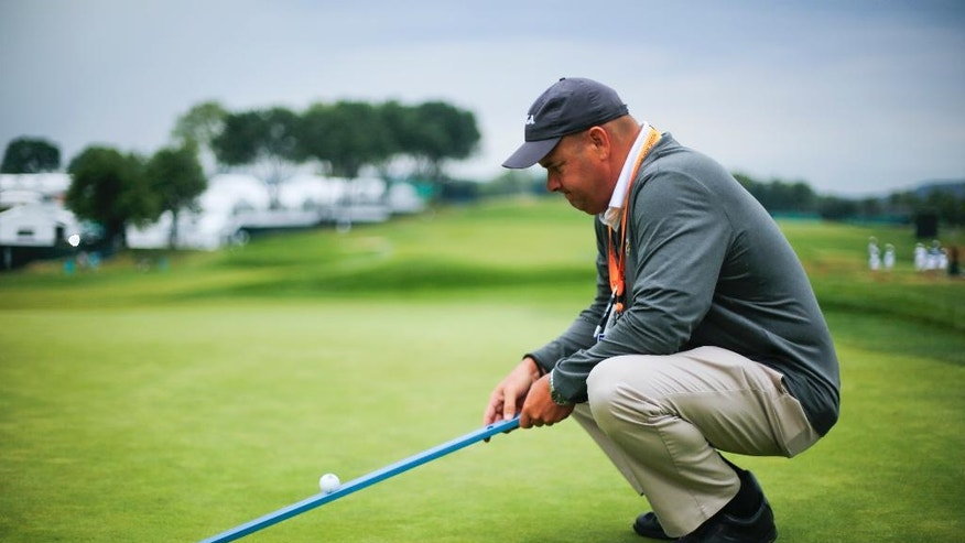 "Darin Bevard with the USGA show off a ""Stimpmeter"" at the U.S. Open golf championship at Oakmont Country Club on Wednesday, June 15, 2016, in Oakmont, Pa. It's called a ""Stimpmeter"" in honor of inventor Edward S. Stimpson and in a nice bit of serendipity, the device traces its origins back to storied Oakmont Country Club, site of this season's second major. No matter how much golfers bellyache during the week, the ramp, slightly less than 2 inches wide, will have the last word on how fast the greens are running. (AP Photo/Gene J. Puskar)"