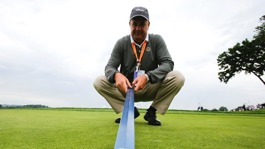 "Darin Bevard with the USGA show off a ""Stimpmeter"" the U.S. Open golf championship at Oakmont Country Club on Wednesday, June 15, 2016, in Oakmont, Pa. It's called a ""Stimpmeter"" in honor of inventor Edward S. Stimpson and in a nice bit of serendipity, the device traces its origins back to storied Oakmont Country Club, site of this season's second major. No matter how much golfers bellyache during the week, the ramp, slightly less than 2 inches wide, will have the last word on how fast the greens are running. (AP Photo/Gene J. Puskar)"