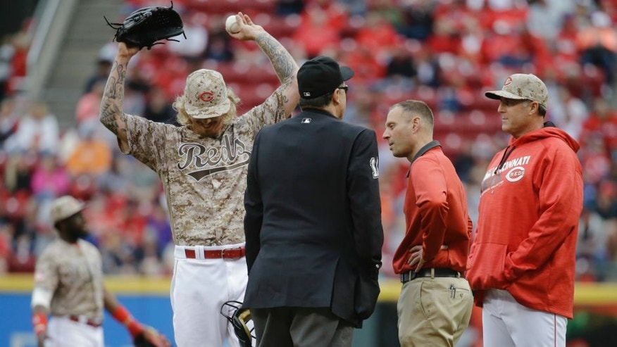 Cincinnati Reds starting pitcher John Lamb, left, reacts alongside manager Bryan Price, right, and umpire Tony Randazzo, center, after being hit by a line drive from Seattle Mariners' Dae-Ho Lee in the fourth inning of a baseball game, Saturday, May 21, 2016, in Cincinnati. (AP Photo/John Minchillo)