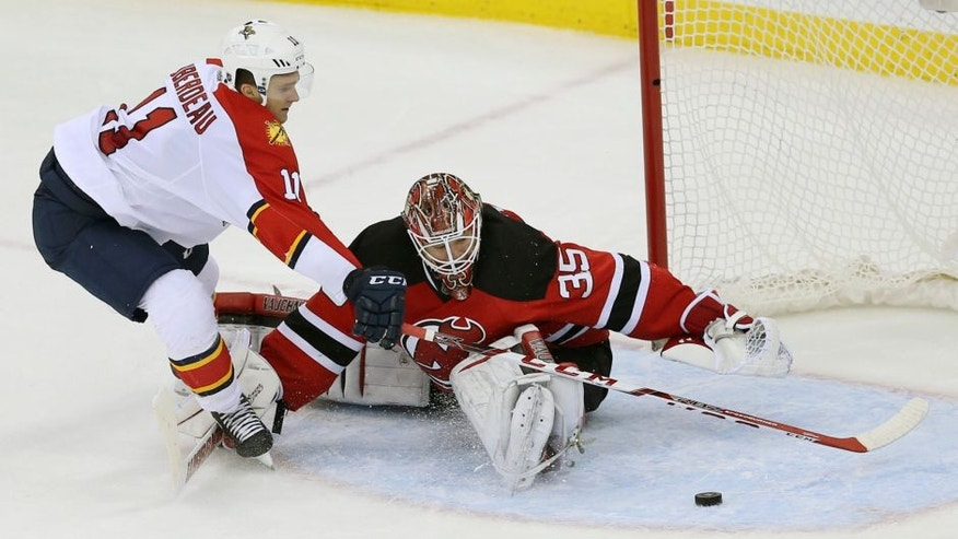 Florida Panthers left wing Jonathan Huberdeau (11) is unable to score on a penalty shot as New Jersey Devils goalie Cory Schneider (35) makes a save during the second period of an NHL hockey game Sunday, Dec. 6, 2015, in Newark, N.J. (AP Photo/Mel Evans)