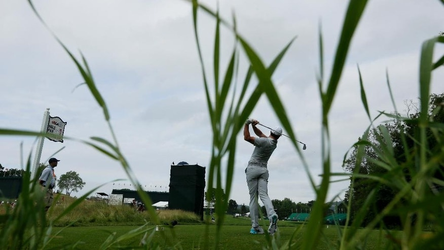Rory McIlroy, of Northern Ireland, watches his tee shot on the 16th hole during the rain delayed first round of the U.S. Open golf championship at Oakmont Country Club on Friday, June 17, 2016, in Oakmont, Pa. (AP Photo/Charlie Riedel)