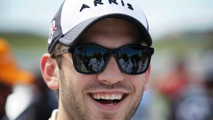 Daniel Suarez laughs as he waits in pit row before qualifying for the NASCAR Truck Series auto race, Saturday, June 18, 2016, at Iowa Speedway in Newton, Iowa. (AP Photo/Charlie Neibergall)