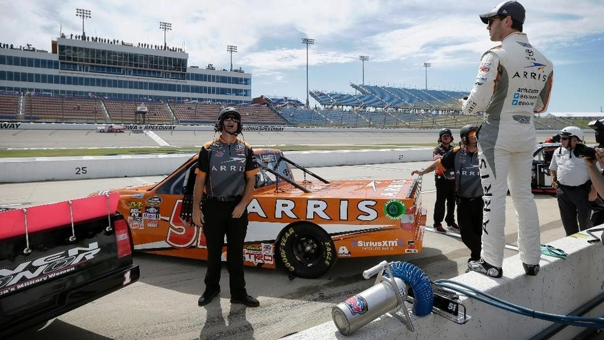 Daniel Suarez, right, watches qualifying for the NASCAR Truck Series auto race, Saturday, June 18, 2016, at Iowa Speedway in Newton, Iowa. (AP Photo/Charlie Neibergall)
