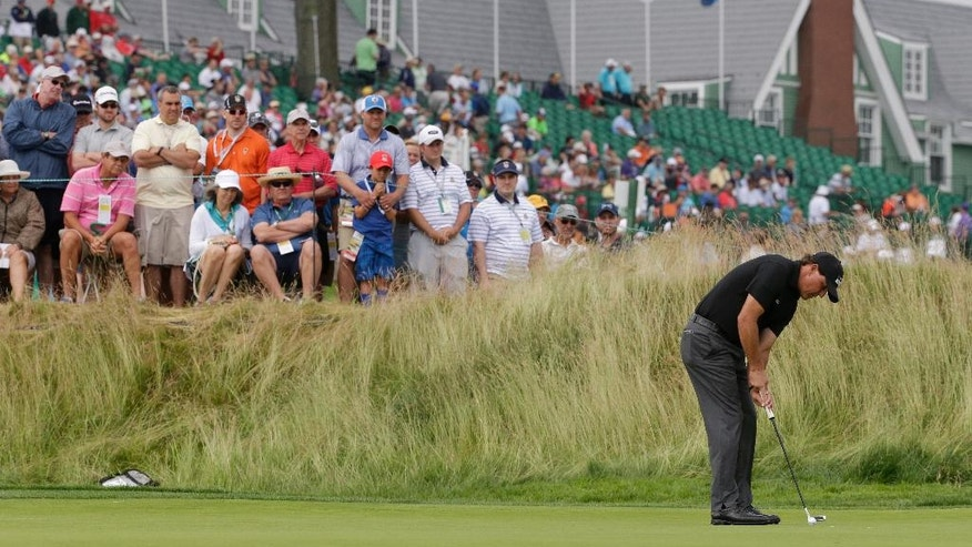 Phil Mickelson putts on the 11th hole during the rain delayed first round of the U.S. Open golf championship at Oakmont Country Club on Friday, June 17, 2016, in Oakmont, Pa. (AP Photo/Gene J. Puskar)