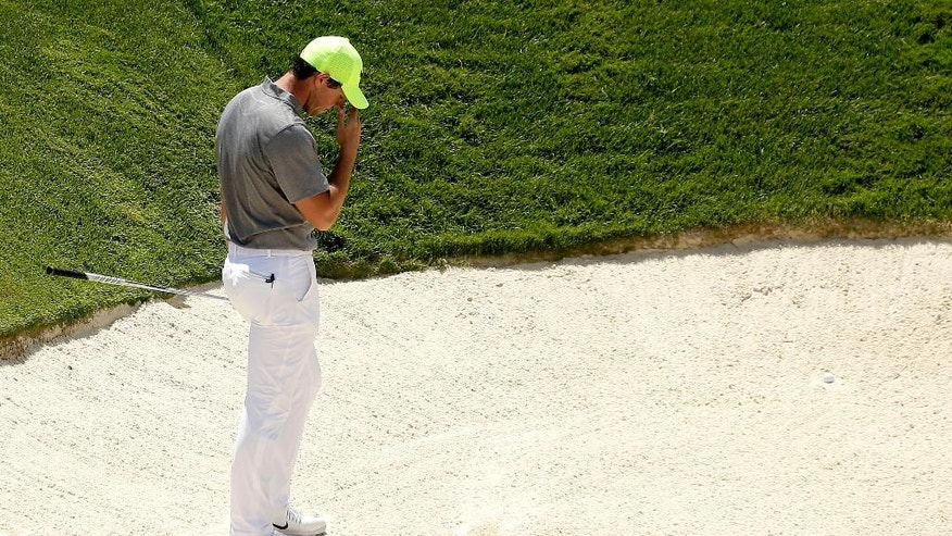 Rory McIlroy, of Northern Ireland, reacts after leaving his first bunker shot in the sand on the ninth hole during the rain delayed second round of the U.S. Open golf championship at Oakmont Country Club on Saturday, June 18, 2016, in Oakmont, Pa. (AP Photo/Charlie Riedel)