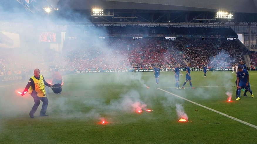 Flares are thrown onto the pitch during the Euro 2016 Group D soccer match between the Czech Republic and Croatia at the Geoffroy Guichard stadium in Saint-Etienne, France, Friday, June 17, 2016. Czech Republic salvaged a 2-2 draw with Croatia in a game marred by a temporary suspension when flares were thrown onto the pitch and Croatia fans fought among themselves. (AP Photo/Darko Bandic)