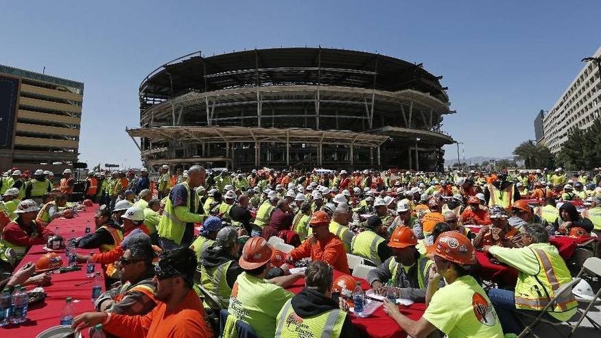 FILE - In this April 7, 2015, file photo, construction workers eat lunch by an MGM arena being built behind the New York-New York casino-hotel in Las Vegas. Hockey fans and civic boosters are getting excited at the prospect of the NHL coming to Las Vegas. A person with direct knowledge of the decision told The Associated Press that the league has settled on the entertainment capital as the home for its next expansion team, provided organizers can come up with a $500 million fee.(AP Photo/John Locher, FIle)