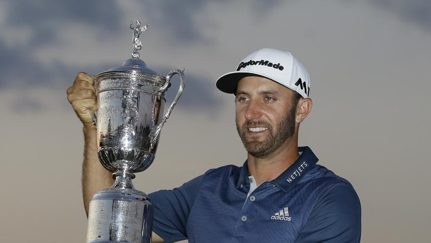 Dustin Johnson holds the trophy after winning the U.S. Open golf championship at Oakmont Country Club on Sunday, June 19, 2016, in Oakmont, Pa. (AP Photo/John Minchillo)