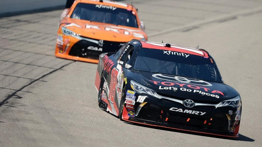 Sam Hornish Jr. (18) races ahead of Daniel Suarez, rear, during the NASCAR Xfinity Series auto race, Sunday, June 19, 2016, at Iowa Speedway in Newton, Iowa. (AP Photo/Charlie Neibergall)