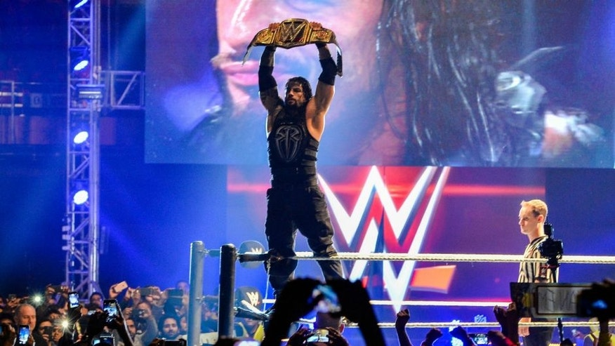 In this photograph taken on January 15, 2016, wrestler Roman Reigns holds up the Championship Belt during the World Wrestling Entertainment (WWE) Live India Tour in New Delhi. Enthusiastic fans flocked to the event as WWE returned to the country after an interval of 13 years. AFP PHOTO/ CHANDAN KHANNA / AFP / Chandan Khanna (Photo credit should read CHANDAN KHANNA/AFP/Getty Images)