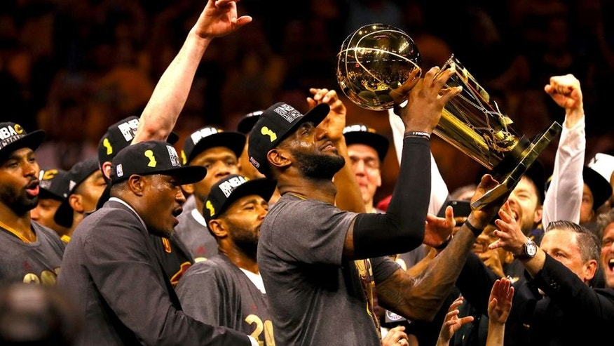 OAKLAND, CA - JUNE 19: LeBron James #23 of the Cleveland Cavaliers holds the Larry O'Brien Championship Trophy after defeating the Golden State Warriors 93-89 in Game 7 of the 2016 NBA Finals at ORACLE Arena on June 19, 2016 in Oakland, California. NOTE TO USER: User expressly acknowledges and agrees that, by downloading and or using this photograph, User is consenting to the terms and conditions of the Getty Images License Agreement. (Photo by Ezra Shaw/Getty Images)