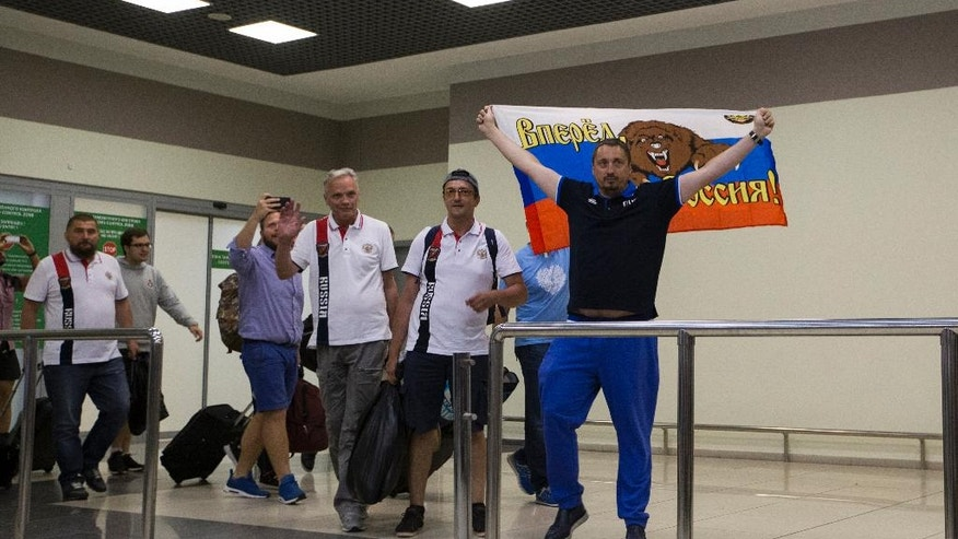 Alexander Shprygin, the leader of a Russian fan group, right, holds a Russian flag depicting a bear and reading Russia Forward, as a group of soccer fans deported from France arrived in Moscow, Russia, Saturday, June 18, 2016. A group of 20 Russian soccer fans have been deported from France, leaving on a flight to Moscow after French authorities accused them of being involved in hooliganism. (AP Photo/Alexander Zemlianichenko)
