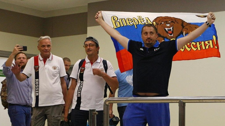 Alexander Shprygin, the leader of a Russian fan group, holds a Russian flag depicting a bear and reading Russia Forward, as a group of soccer fans deported from France arrived in Moscow, Russia, Saturday, June 18, 2016. A group of 20 Russian soccer fans were deported from France, after French authorities accused them of being involved in hooliganism. (AP Photo/Alexander Zemlianichenko)