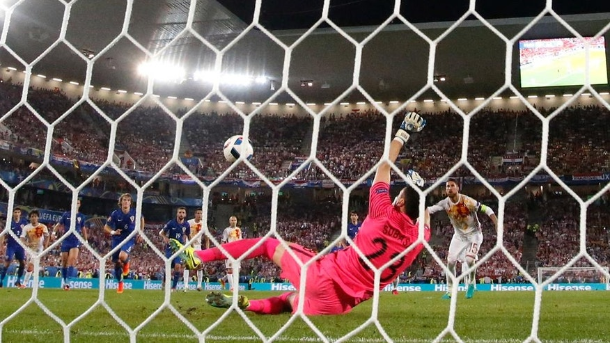 Croatia goalkeeper Danijel Subasic, foreground, stops a penalty kick from Spain's Sergio Ramos, right, during the Euro 2016 Group D soccer match between Croatia and Spain at the Nouveau Stade in Bordeaux, France, Tuesday, June 21, 2016. (AP Photo/Manu Fernandez)