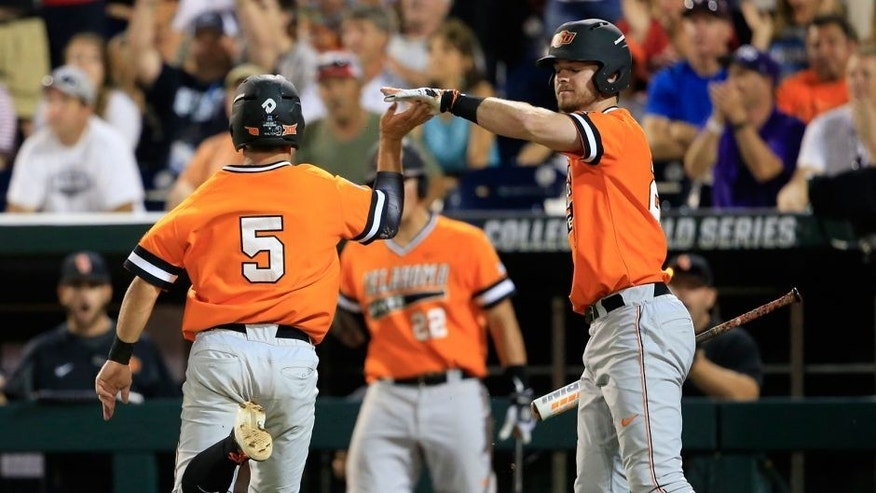 Oklahoma State's Donnie Walton, left, is congratulated by Conor Costello after scoring on a single by Garrett Benge during the fourth inning of an NCAA College World Series baseball game against Arizona, Monday, June 20, 2016, in Omaha, Neb. (AP Photo/Nati Harnik)