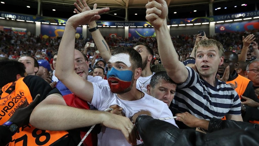 Russian supporters are pushed back as they shout at their team after Russia lost the Euro 2016 Group B soccer match between Russia and Wales at the Stadium municipal in Toulouse, France, Monday, June 20, 2016. (AP Photo/Hassan Ammar)
