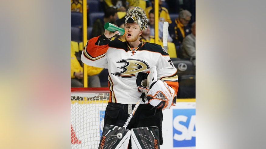 FILE - In this April 25, 2016 file photo, Anaheim Ducks goalie Frederik Andersen, of Denmark, takes a drink in the second period of Game 6 against the Nashville Predators in an NHL hockey first-round Stanley Cup playoff in Nashville, Tenn.  With the salary cap expected to remain flat, the Maple Leafs and Panthers were opportunistic in giving up draft picks to acquire NHL-caliber help. The Maple Leafs traded first- and second-round picks to the Anaheim Ducks for Andersen and signed the 26-year-old goaltender to a $25 million, five-year deal.  AP Photo/Mark Humphrey)