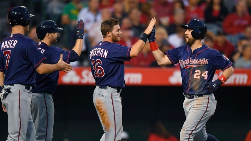 The Minnesota Twins' Trevor Plouffe (right) is congratulated by Joe Mauer (left), Brian Dozier (second from left) and Robbie Grossman after hitting a three-run home run during the third inning against the Los Angeles Angels on Monday, June 13, 2016, in Anaheim, Calif.