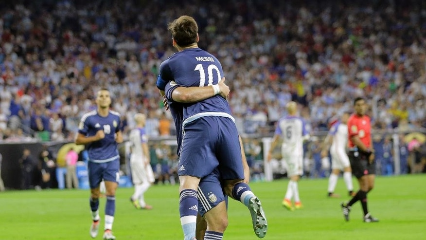 Argentina's Gonzalo Higuain picks up teammate Lionel Messi (10) as he celebrates his goal against the United States during a Copa America Centenario soccer semifinal, Tuesday, June 21, 2016, in Houston. (AP Photo/Eric Gay)