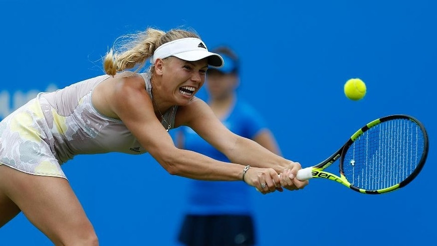 Denmark's Caroline Wozniacki stretches to return to Puerto Rica's Monica Puig during their match in the Eastbourne  International tennis tournament at at Devonshire Park, Eastbourne, England Wednesday June 22, 2016. (Steve Paston/PA via AP)  UNITED KINGDOM OUT