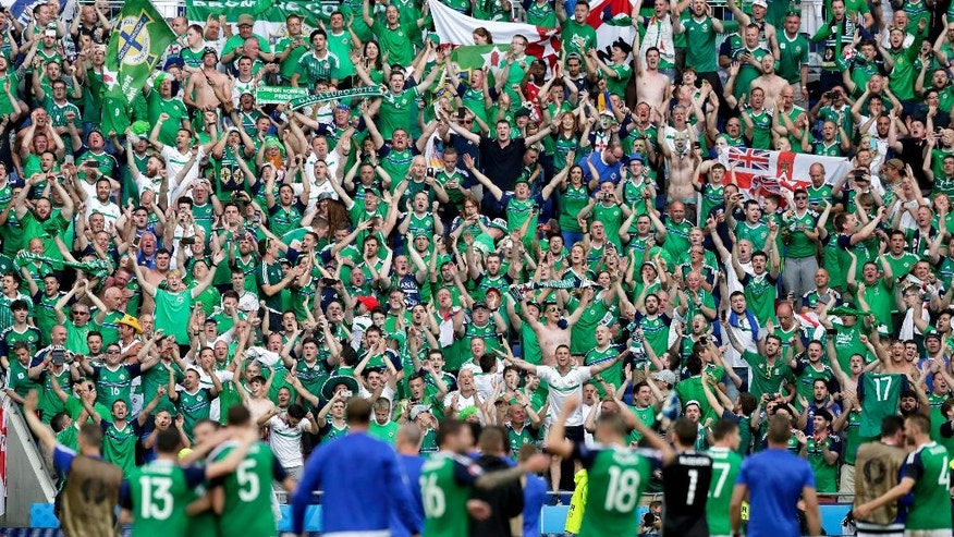FILE - In this Thursday, June 16, 2016 file photo, Northern Ireland's supporters celebrate with players, at the end of the Euro 2016 Group C soccer match between Ukraine and Northern Ireland at the Grand Stade in Decines-­Charpieu, near Lyon, France. Will Grigg hasn't had any playing time yet at the European Championship, but a catchy chant featuring the Northern Ireland striker is lighting up the tournament. The 24-year-old is one of the hits of Euro 2016 thanks to the chant that has gone viral around grounds and on social media even as he remained rooted to the bench. (AP Photo/Pavel Golovkin, File)