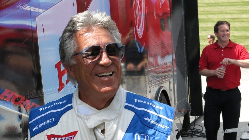 Retired IndyCar driver Mario Andretti walks out of a trailer at the Road America track in Elkhart Lake, Wis. on June 22, 2016.  IndyCar is returning to Road America for the first time since 2007 this Sunday, June 26, 2016. Tony Kanaan and Andretti, who won at the road course three times in the 1980s, are among the drivers eager for the return of the open wheel series to the sprawling, 4-mile track on a woody campus that resembles a campground.  (AP Photo/Genaro C. Armas)