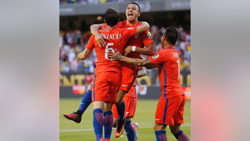 Chile's Jose Pedro Fuenzalida (6) celebrates his goal as he jumps in the arms of Chile's Eduardo Vargas (11) during a Copa America Centenario semifinal soccer match against Colombia, at Soldier Field in Chicago, Wednesday, June 22, 2016. (AP Photo/Charles Rex Arbogast)