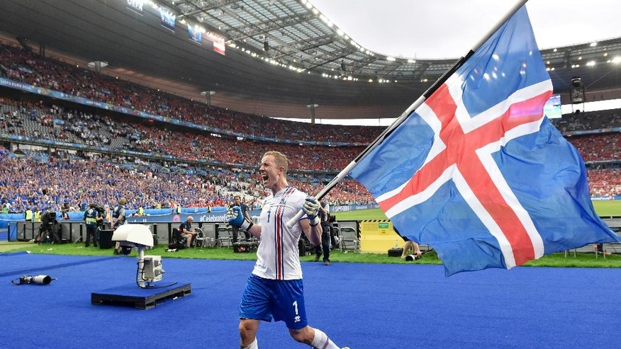 Iceland goalkeeper Hannes Halldorsson holds his country's flag while celebrating after the Euro 2016 Group F soccer match between Iceland and Austria at the Stade de France in Saint-Denis, north of Paris, France, Wednesday, June 22, 2016. (AP Photo/Martin Meissner)