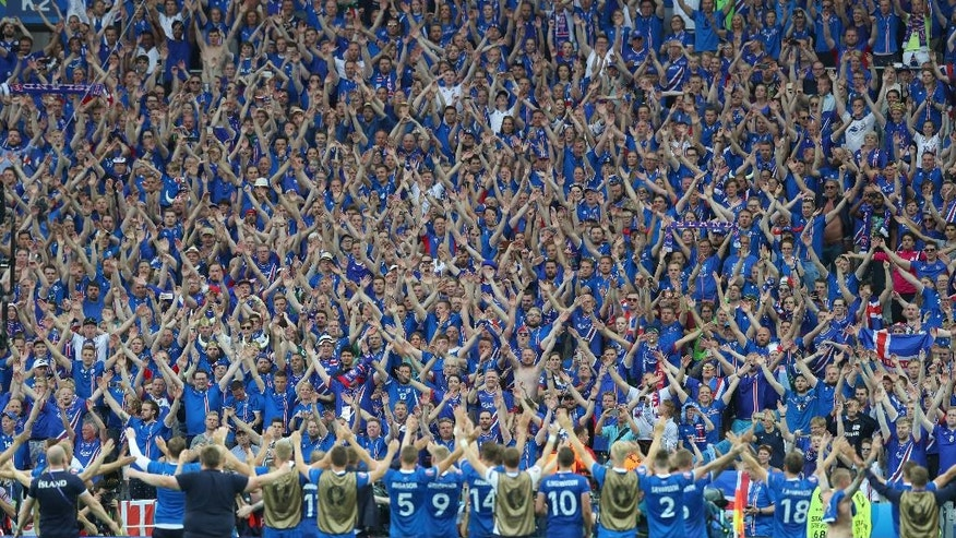 Iceland's players celebrate their victory with their supporters at the end the Euro 2016 Group F soccer match between Iceland and Austria at the Stade de France in Saint-Denis, north of Paris, France, Wednesday, June 22, 2016. Iceland, the smallest nation at the European Championship, surprisingly qualified for the knockout stage after beating Austria 2-1 in Paris thanks to a stoppage-time winner by Arnor Ingvi Traustason.(AP Photo/Thibault Camus)