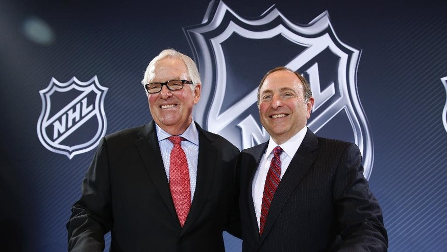 NHL Commissioner Gary Bettman, right, and Bill Foley pose for photographers during a news conference Wednesday, June 22, 2016, in Las Vegas. Bettman announced an expansion franchise to Las Vegas after the league's board of governors met in Las Vegas. Foley is the majority owner of the team. (AP Photo/John Locher)