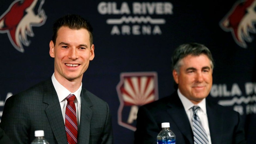 Newly appointed Arizona Coyotes general manager John Chayka speaks at a news conference announcing his promotion as head coach Dave Tippett listens, Thursday, May 5, 2016, in Glendale, Ariz. Chayka is the youngest GM in NHL history. (AP Photo/Matt York)