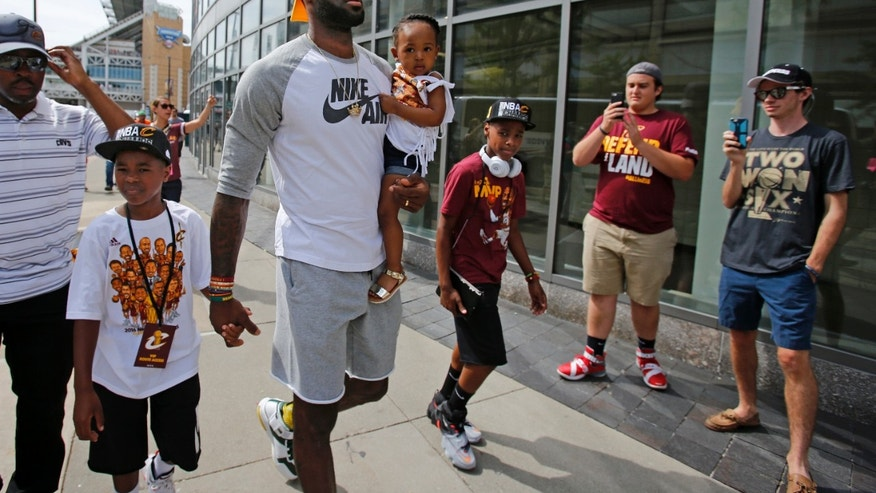 Cleveland Cavaliers' LeBron James, center, arrives at the Quicken Loans Arena with his children before a parade celebrating the Cavaliers' NBA Championship in downtown Cleveland, Wednesday, June 22, 2016.